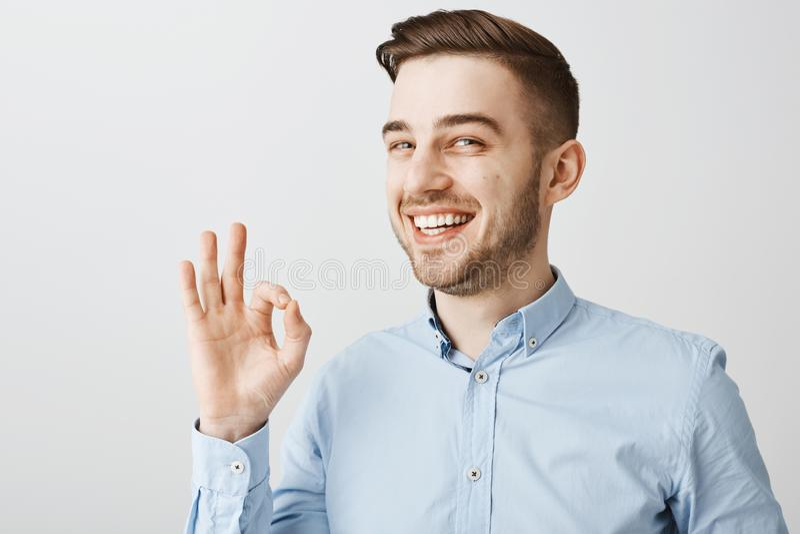 保证工友工作的人及时做 在优秀蓝色的衬衣的喜悦的悦目年轻男性显示好或 库存照片