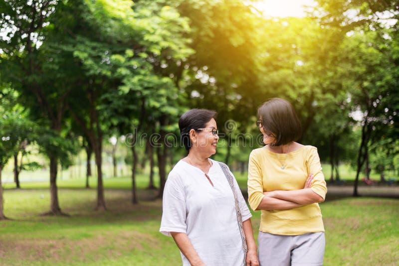 保重,并且支持概念,中部画象变老了有一起站立和拥抱室外,愉快的女儿的亚裔妇女和sm 免版税库存图片