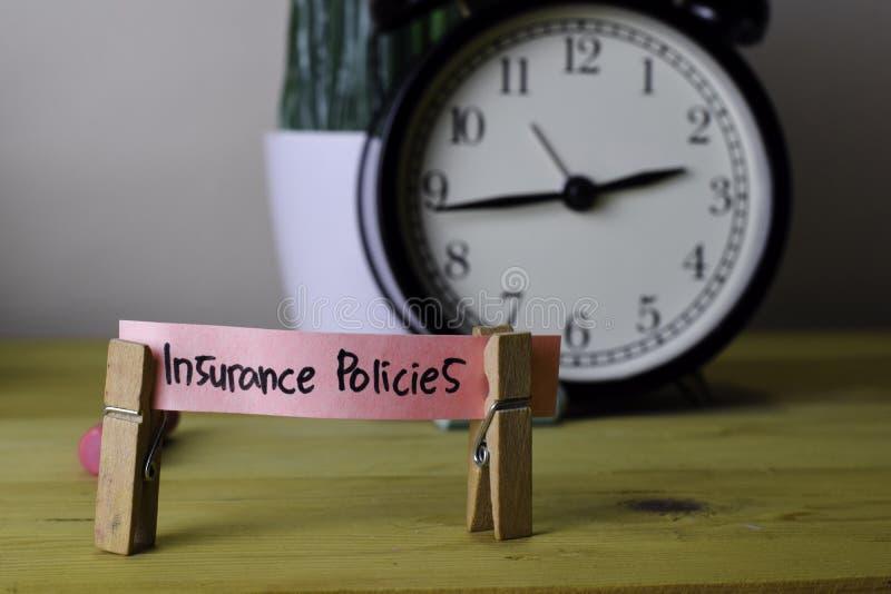 保险单 在稠粘的笔记的手写在木办公桌上的服装扣子 免版税库存照片