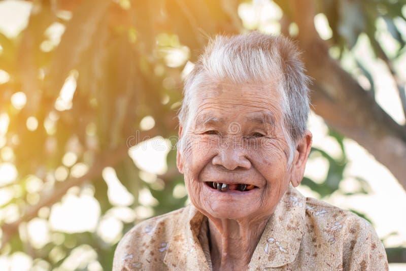 保险概念的老人:亚裔老妇人画象微笑着与她的黑牙以愉快对室外在晴朗 库存照片