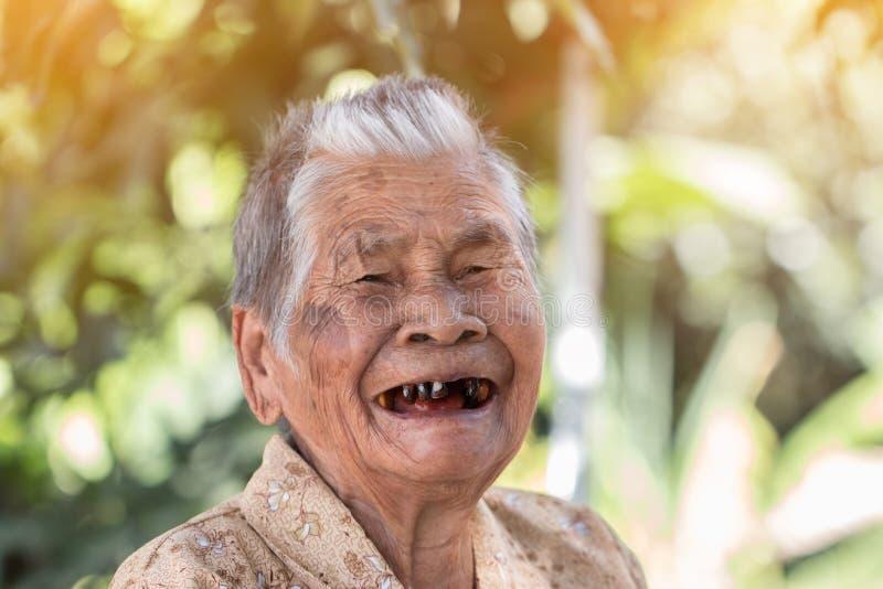保险概念的老人:亚裔老妇人画象微笑着与她的黑牙以愉快对室外在晴朗 图库摄影
