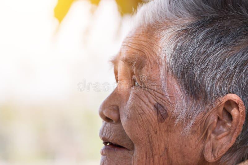 保险概念的老人:单独坐与她的黑牙的亚裔老妇人画象在室外在好日子 免版税库存图片