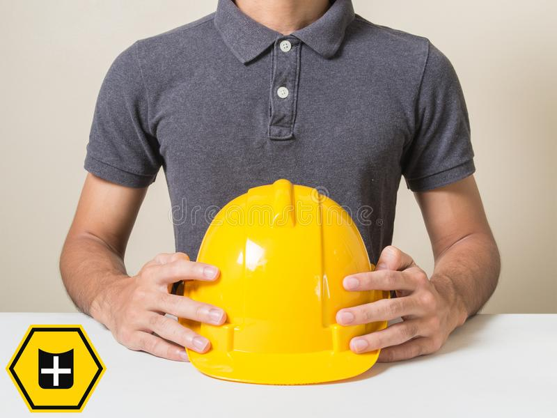 保险盾拿着安全工作者的象人保护盔甲建造者设备建筑建筑师工业概念与 图库摄影
