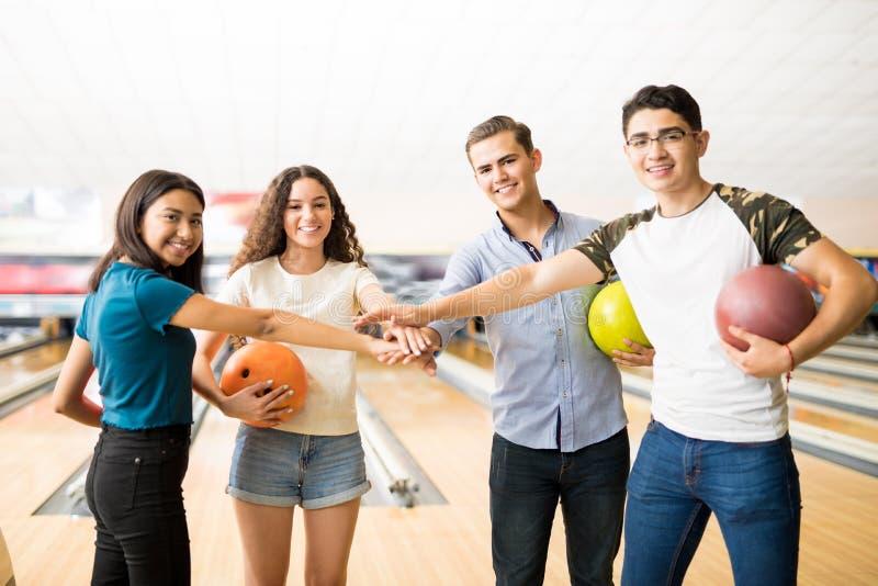 保龄球俱乐部的微笑的青少年的朋友打桩手 库存图片