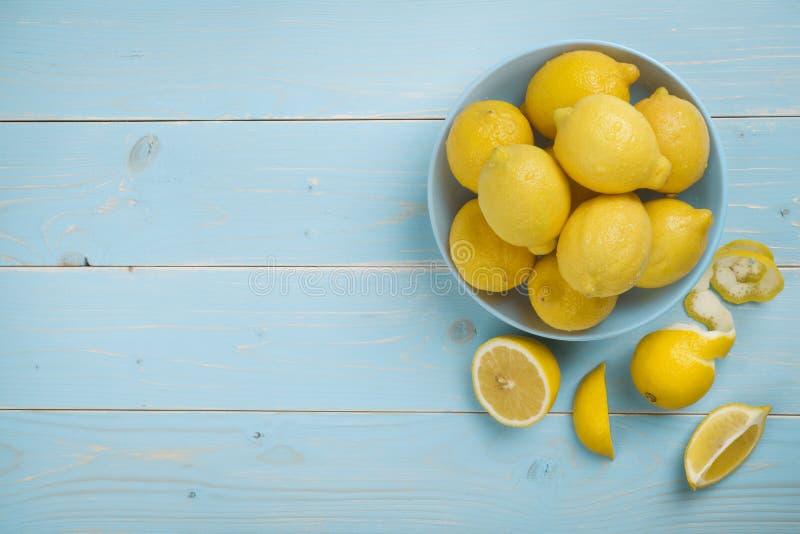 滚保龄球用在蓝色木背景的新鲜的柠檬 顶视图 库存图片