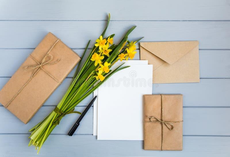 信件、信封、礼物和黄水仙在灰色背景 浪漫假日概念,顶视图,平的位置 库存照片
