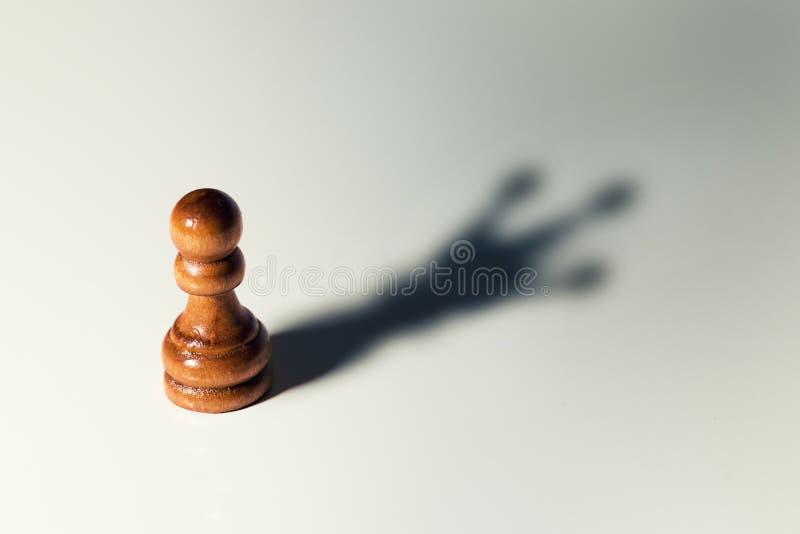 信任自己概念-与国王阴影的棋典当 免版税库存图片
