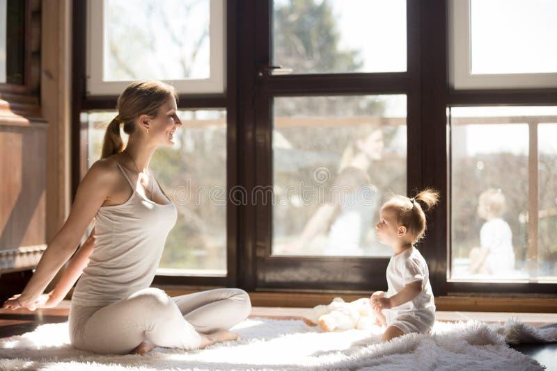 年轻信奉瑜伽者母亲和小女儿开会,健康运动的天 免版税库存照片