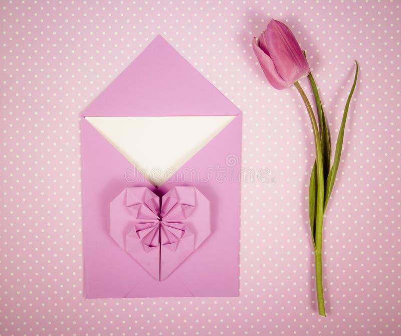 信封、纸心脏和花 桃红色郁金香和origami心脏 库存照片