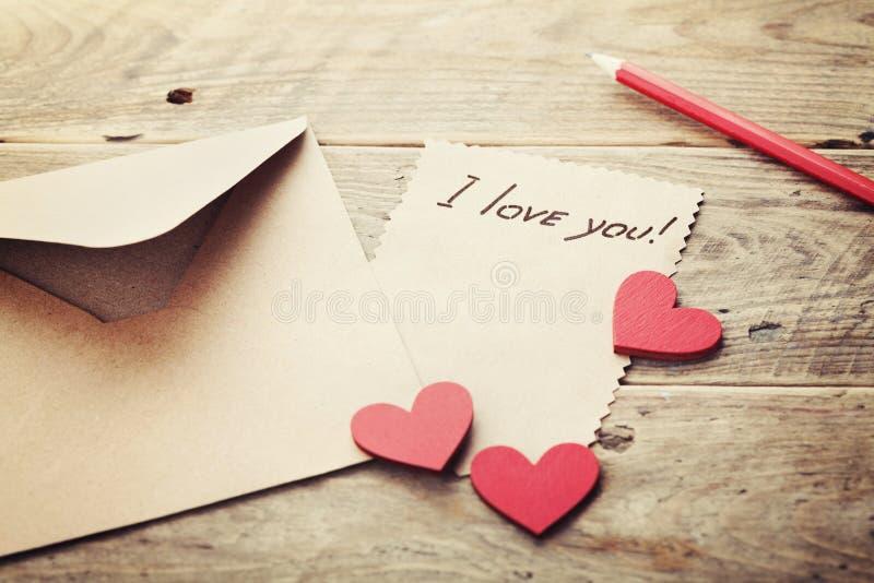 信封或信件、红色心脏和笔记我爱你关于葡萄酒木桌为情人节在减速火箭定调子 免版税库存图片