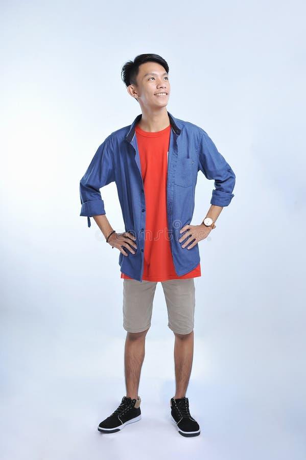 信心亚裔年轻人穿有确信微笑的偶然T恤杉 免版税图库摄影