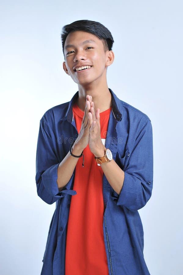 信心亚裔年轻人穿有确信微笑的偶然T恤杉 免版税库存照片