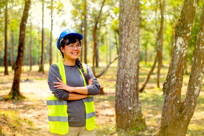 信心的美好和俏丽的工程师妇女展示行动和微笑有自然和森林背景天光的 图库摄影