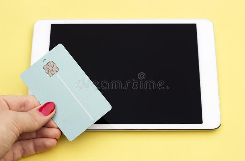 信用卡和片剂在黄色背景,网络购物,星期一网络的概念 免版税库存图片