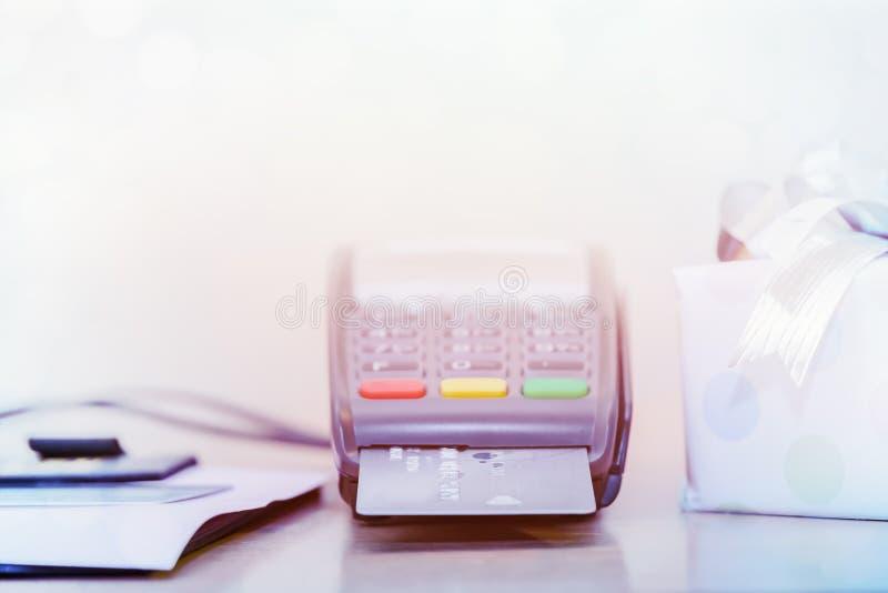 信用卡和芯片读者机器,在桌上与礼物盒浅DOF背景的 免版税图库摄影