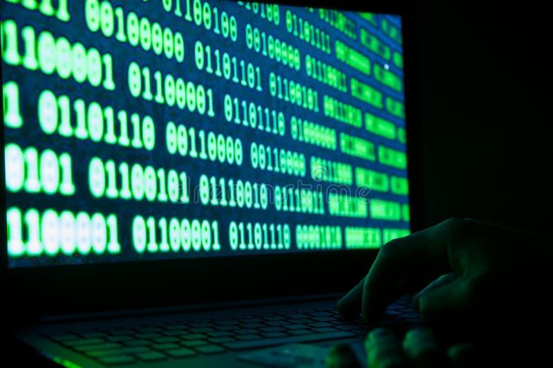 信用卡窃贼,在膝上型计算机键盘,在膝上型计算机屏幕上的二进制数制的信用卡 库存图片