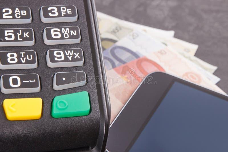 信用卡读者、手机有NFC技术的和curriencies欧元 现金或无钱的付款交易 库存照片