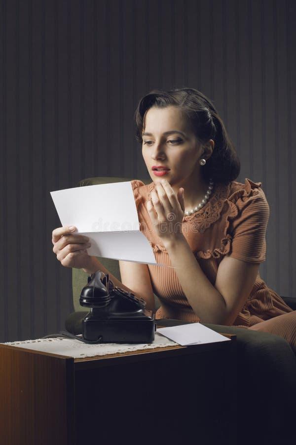 读信的妇女坐扶手椅子 免版税库存照片
