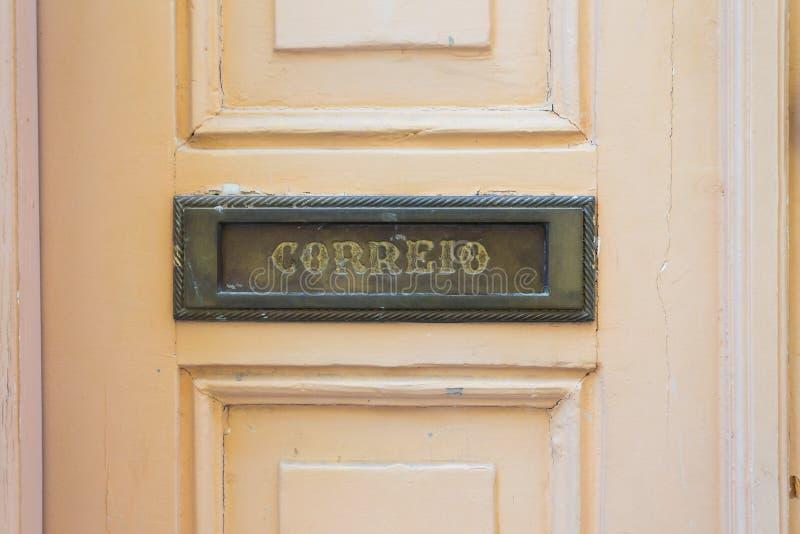 信件开槽在老木门在里斯本,葡萄牙 库存图片