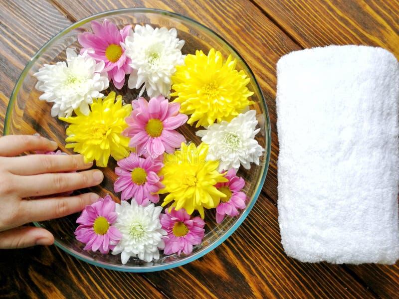 修剪与从花的脚温泉在木背景和白色毛巾 免版税图库摄影