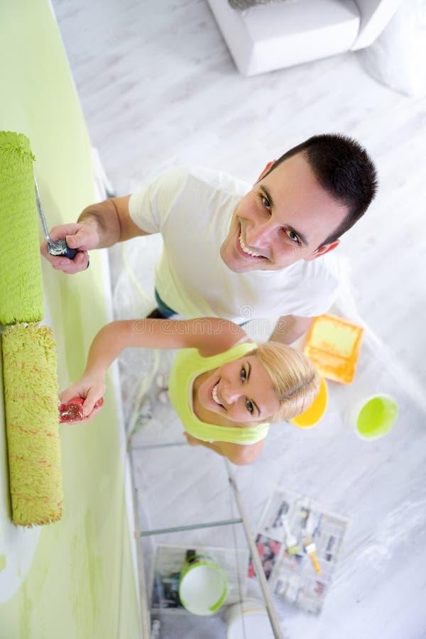 整修在新的家庭绘画墙壁的油漆夫妇 免版税库存照片