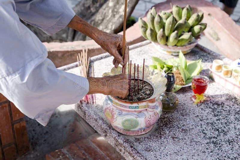 修士在一个特别碗把灼烧的香火棍子放在桌上 免版税库存照片