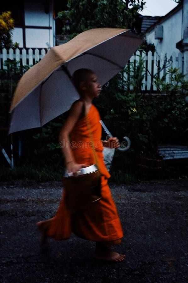 修士在圆他们的清早期间在收集他们的与伞的施舍的镇附近 库存照片