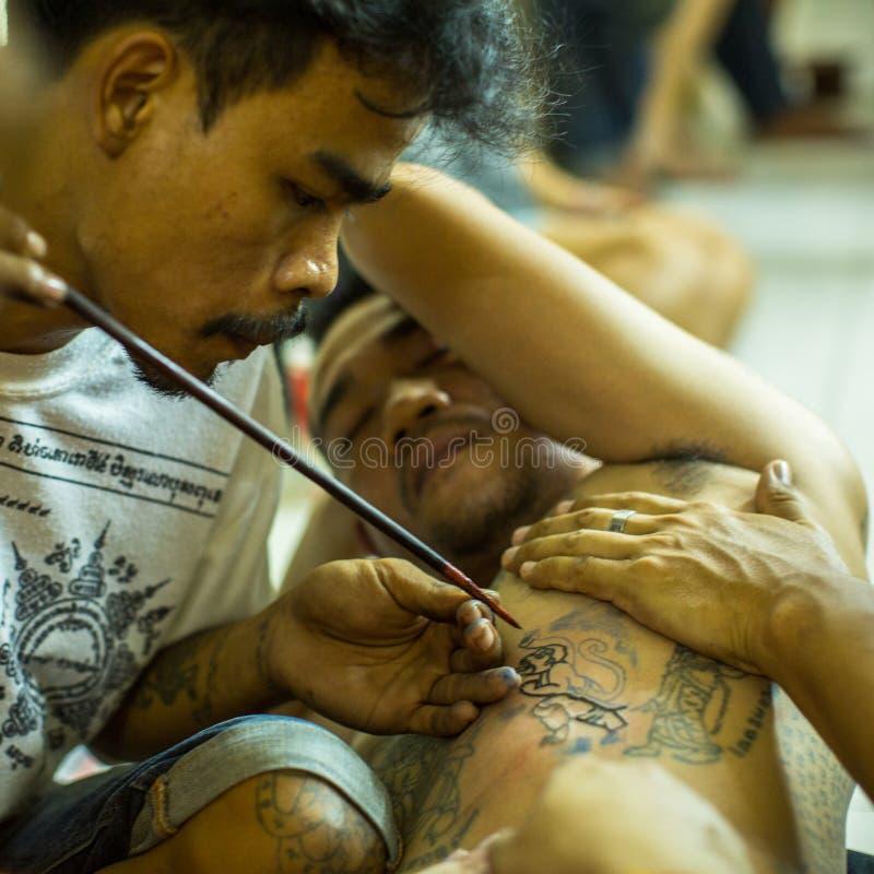 修士在轰隆Pra修道院里做刺字在Wai Kroo大师天仪式期间的传统扬特拉河 免版税库存照片