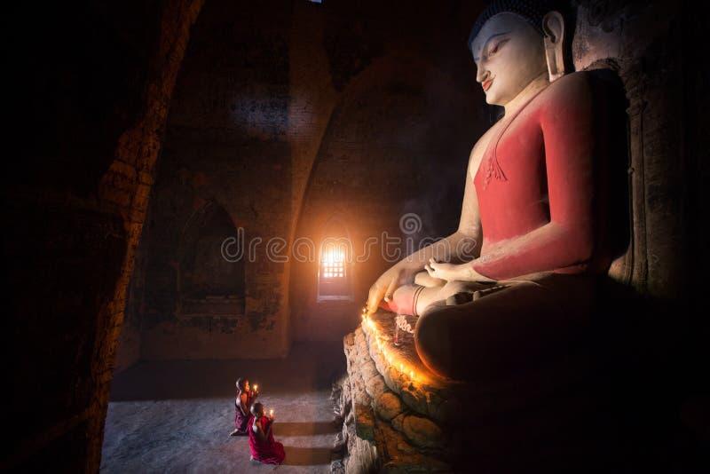 修士在Bagan老镇祈祷菩萨雕象 免版税图库摄影