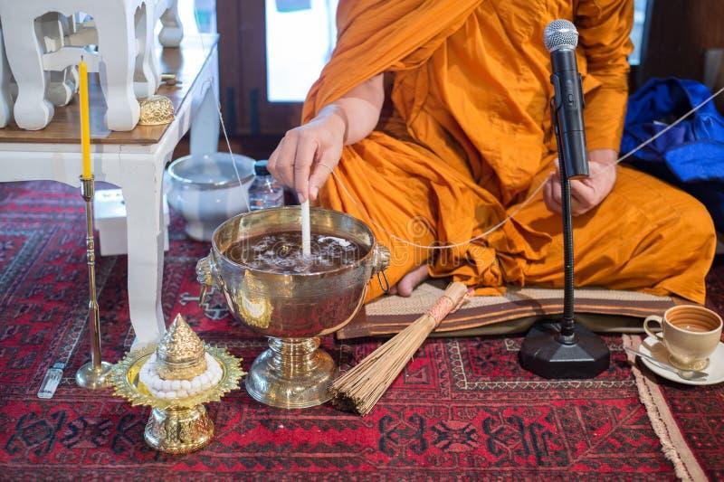 修士执行圣水 关闭和尚` s手倾吐的融解蜡烛撕毁对做的祝福水水在泰国wedd 库存照片