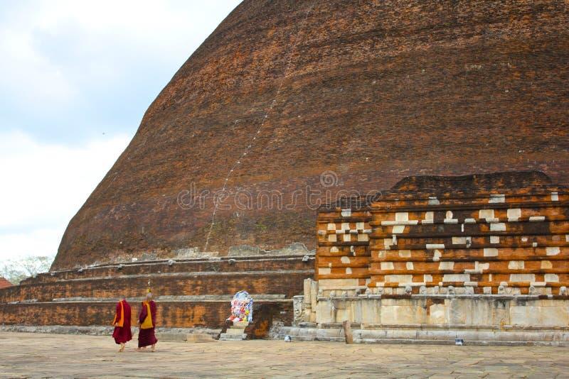 修士步行过去巨大的Jetavanarama Stupa在斯里兰卡 免版税库存图片