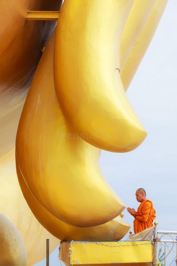 修士说祷告在大金黄菩萨图象的手指在Wat Muang Muang佛教寺庙, Ang皮带,泰国 免版税库存照片