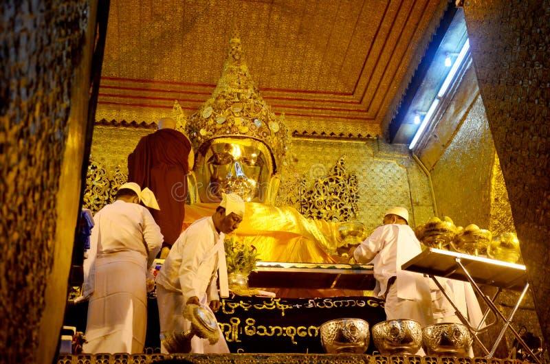 修士洗面孔并且刷菩萨图象的牙在玛哈Myat自治都市 库存照片