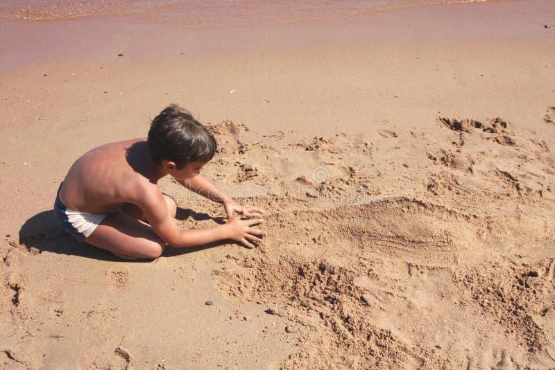 修建图沙子的男孩 免版税库存图片