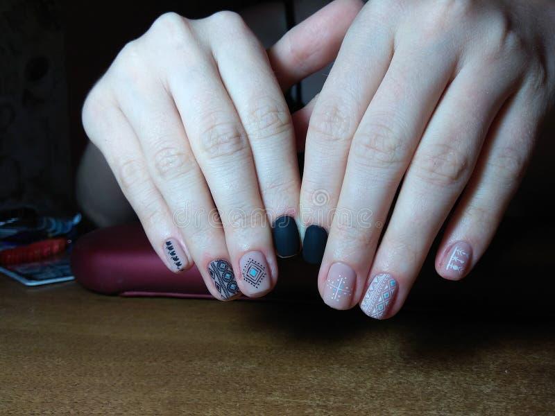 修指甲师在她的手优秀地做了她的工作与一个波兰胶凝体的美好的修指甲,并且客户是愉快的 免版税库存照片