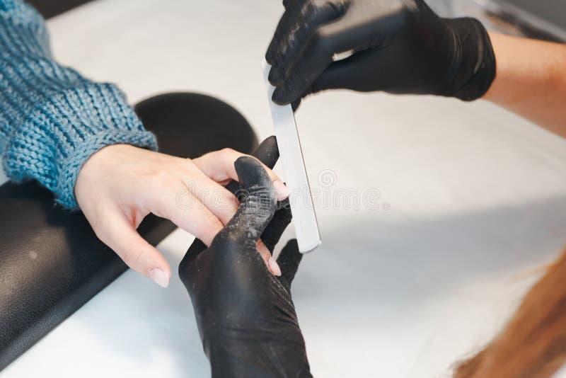修指甲师砍得恨深的伤口客户的钉子 库存图片