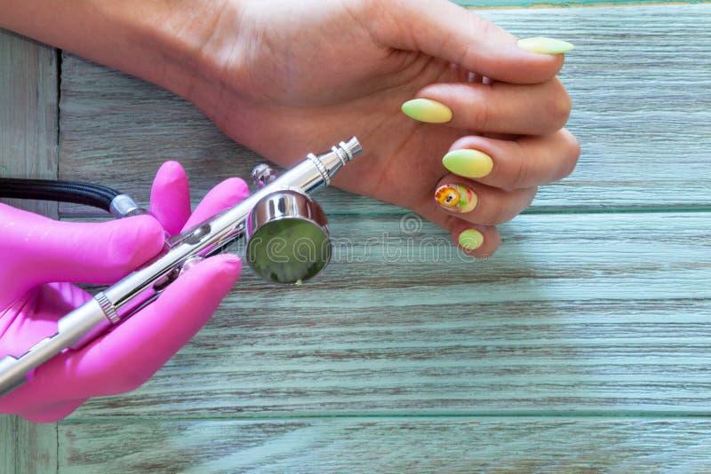 修指甲的大师在一名妇女的钉子做一张图画复活节题材的与气刷 免版税图库摄影
