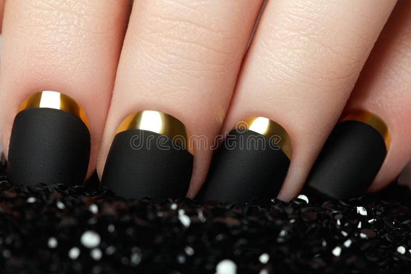修指甲 黑表面无光泽的指甲油 与黑席子的被修剪的钉子 免版税库存图片