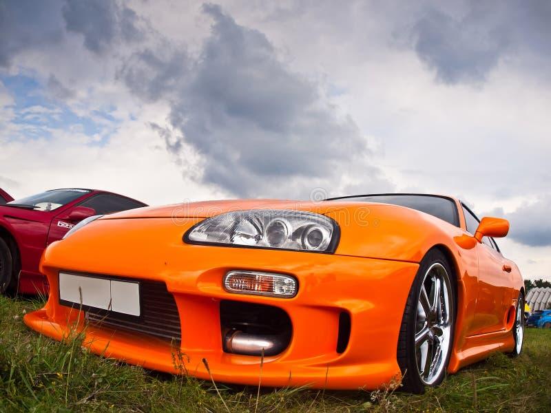 修改过的橙色丰田在上与强有力的引擎 免版税库存照片