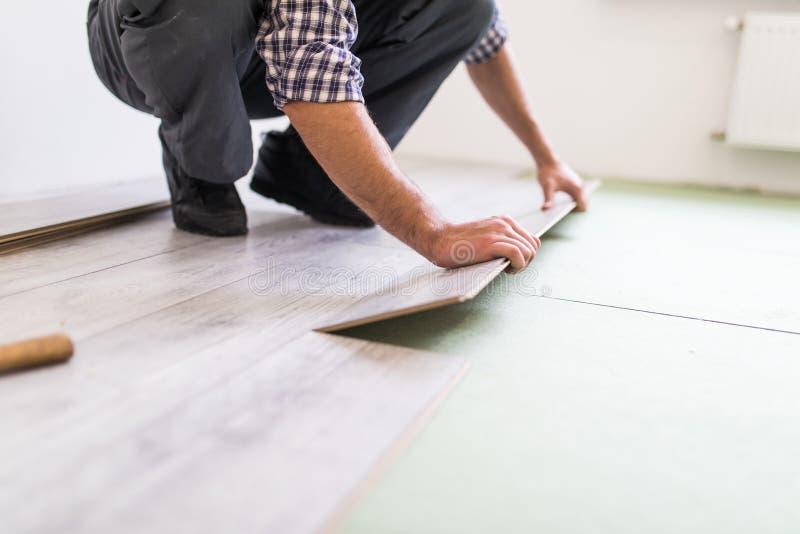 修理、大厦和家庭概念-接近intalling木地板的男性手 库存照片