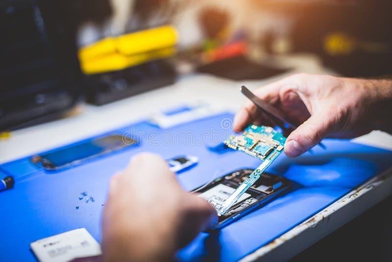 修理一个残破的电话的人 免版税库存照片