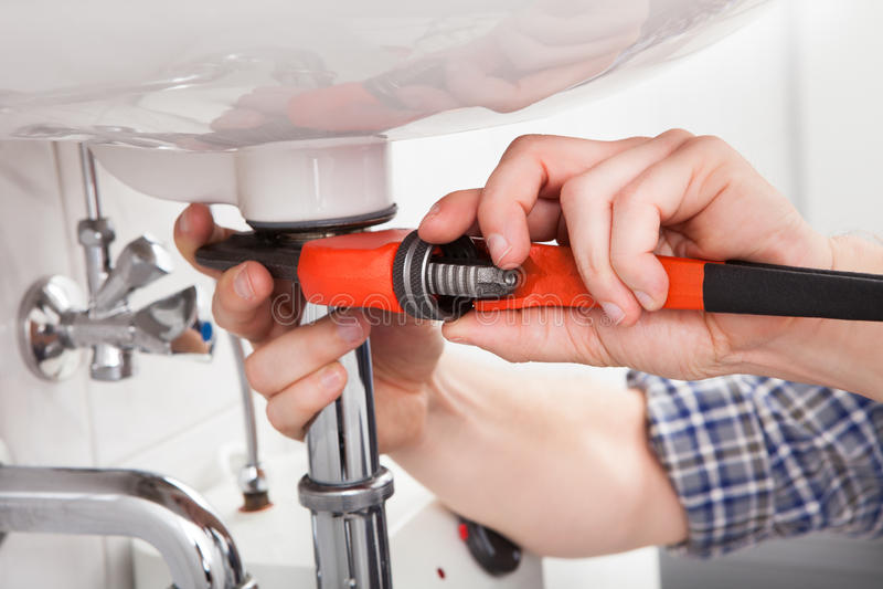 修理一个水槽的年轻水管工在卫生间里 免版税库存图片