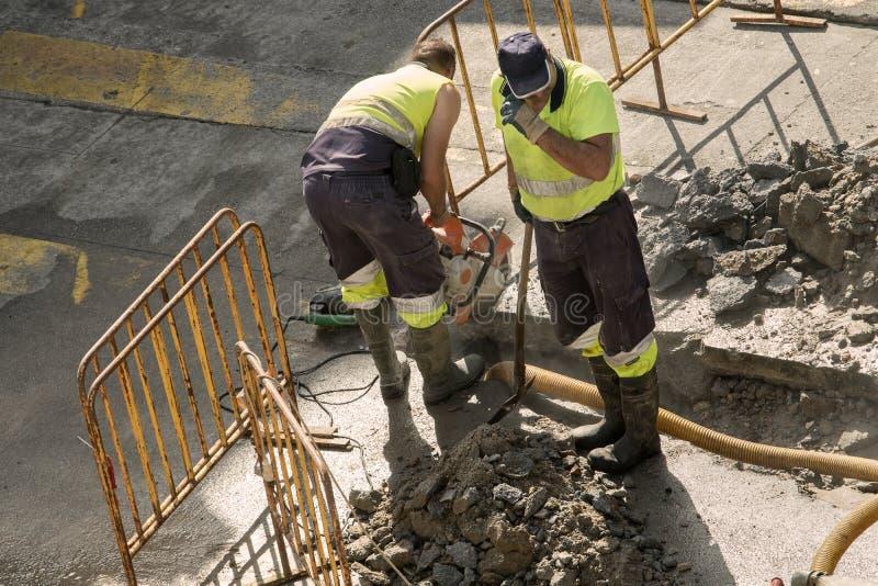 修理一条破裂的导管的建筑工人 免版税库存图片