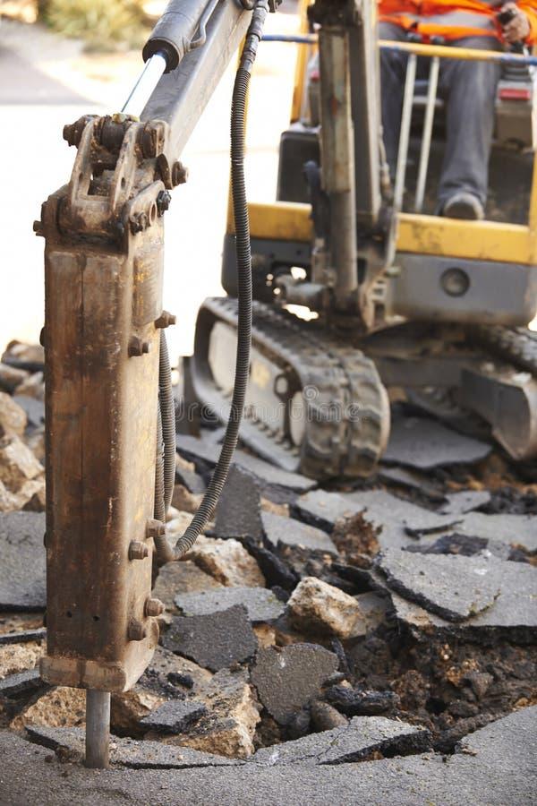 修理与手提凿岩机的建筑工人路面 库存图片