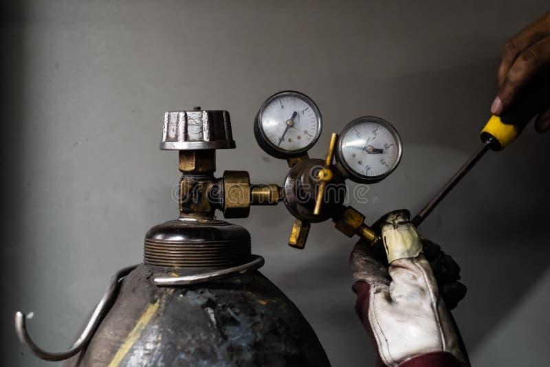 修理丙烷汽油箱 修理压缩的cyl的男性手 免版税图库摄影