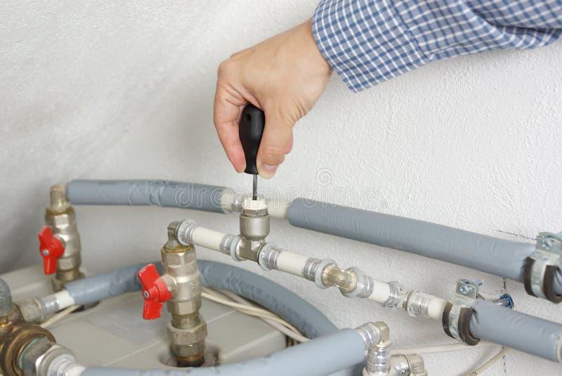 修理中央系统暖气系统的技术员 免版税库存图片
