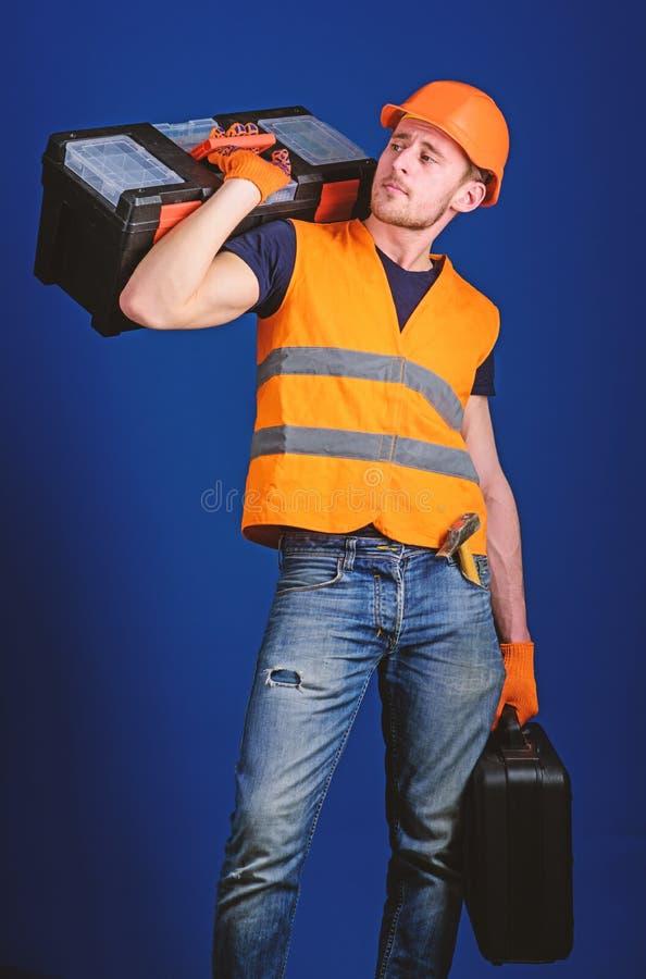 修理公司概念 工作者,修理匠,安装工,在镇静面孔的建造者运载在肩膀的工具箱,准备工作 免版税库存图片