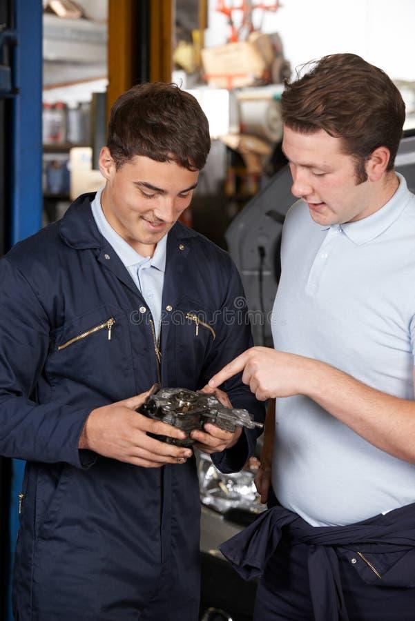 修理发动机的车库帮助的学徒的技工 库存照片