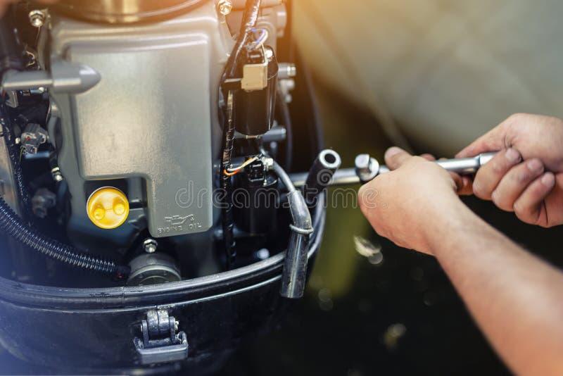 修理可膨胀的汽艇引擎的技工在小船车库 船引擎季节性服务和维护 船马达与 库存图片