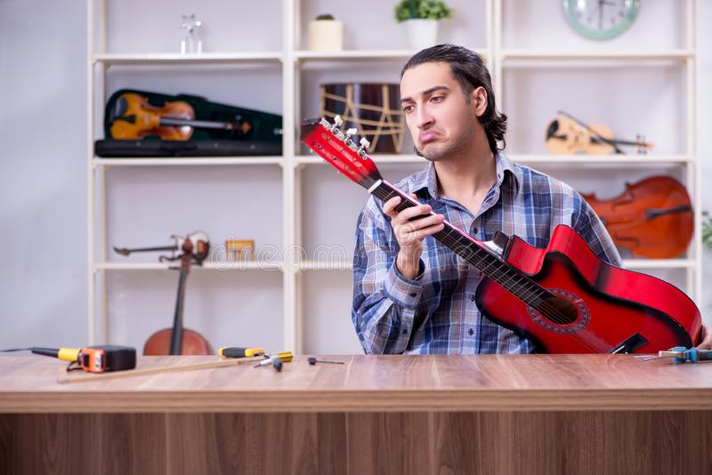 修理吉他的年轻英俊的安装工 库存照片